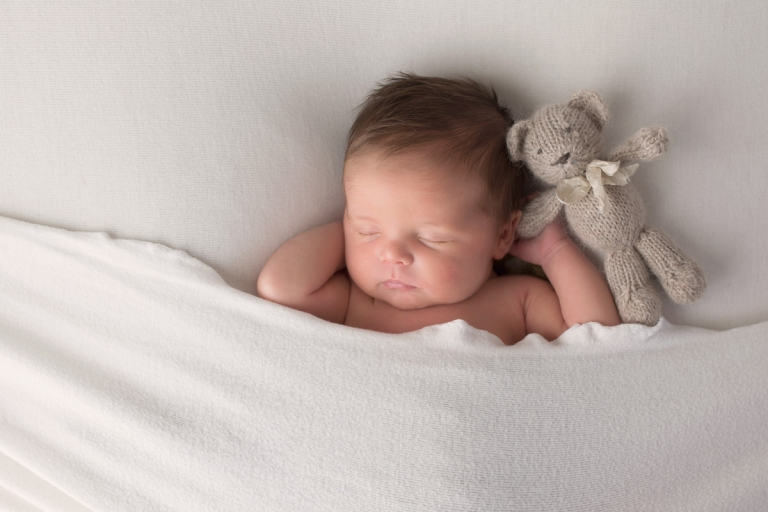 newborn holding a cute teddy