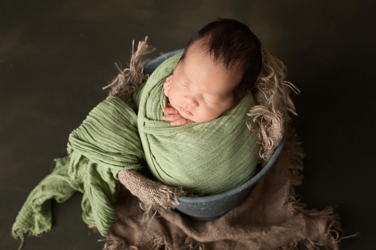 Newborn baby wrapped in green, posed in a bucket
