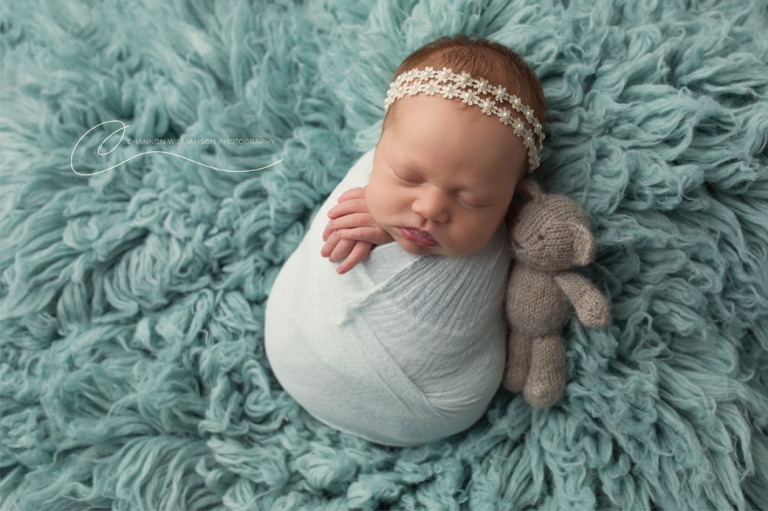 newborn baby wrapped in a bundle with a teddy on a fluffy blue blanket