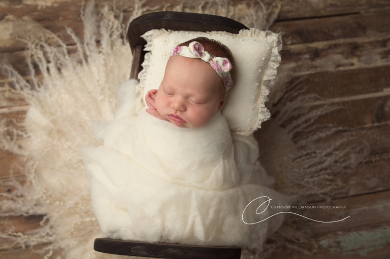 Newborn photography posing in a little bed
