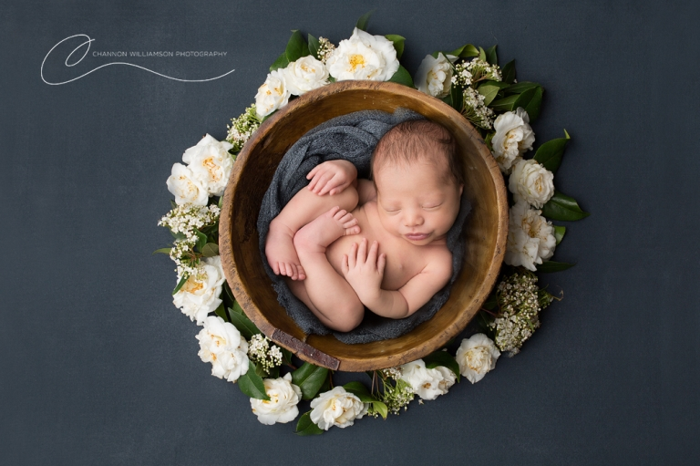 newborn baby curled in a bowl