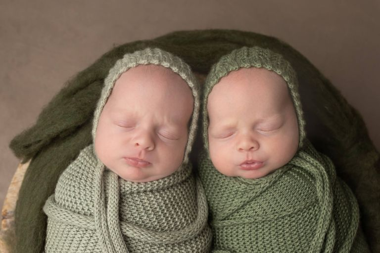 twin girls wrapped in green wearing green bonnets